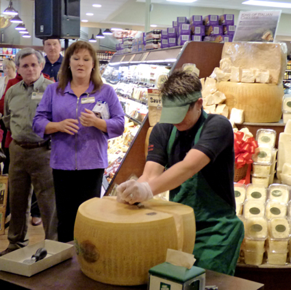 Pam Rosencrans crack a wheel of Parmigiano-Reggiano–signifying the grand opening.
