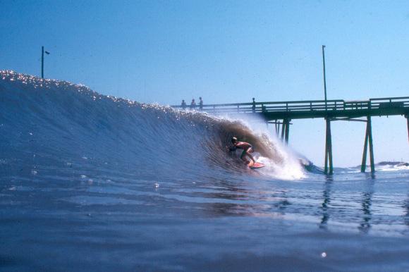 A surfer catches a wave near a pier