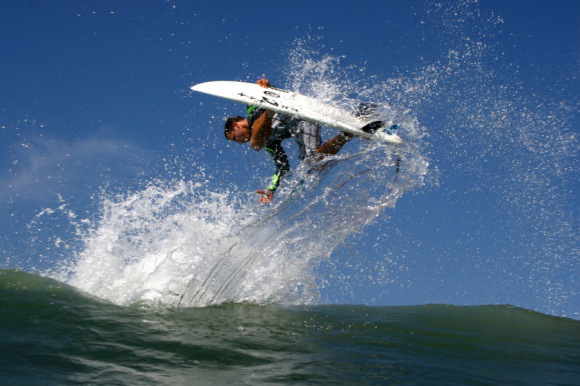 A surfer completes an aerial turn