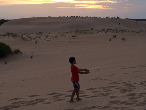 Flying a kite at sunset at Jockey's Ridge State Park.