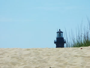 Currituck Beach Lighthouse peering over the edge of a Corolla sand dune.